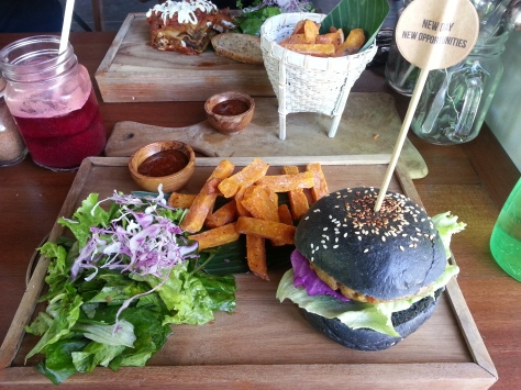 Delicious veggie burger in a charcoal bun with sweet potato fries and a homemade barbeque relish at Peloton Supershop